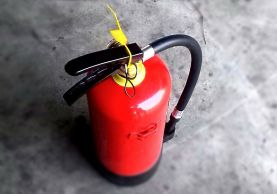 Red fire extinguisher standing on the floor