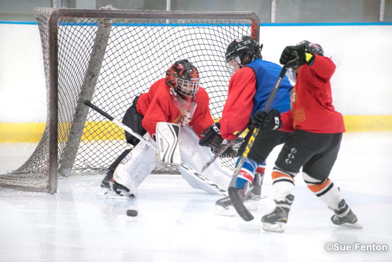 Youth hockey players trying to score while goalie defends goal