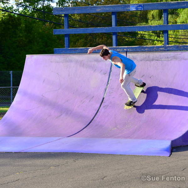 Youth riding skateboard down ramp at skate park