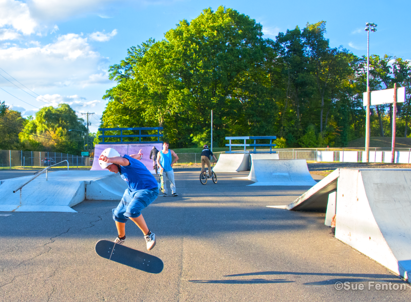 Youth riding skateboards and bicycles at skate park