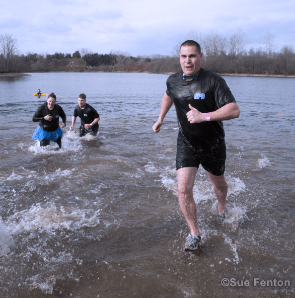 Members of the Newington Police Department exiting the water at polar plunge event
