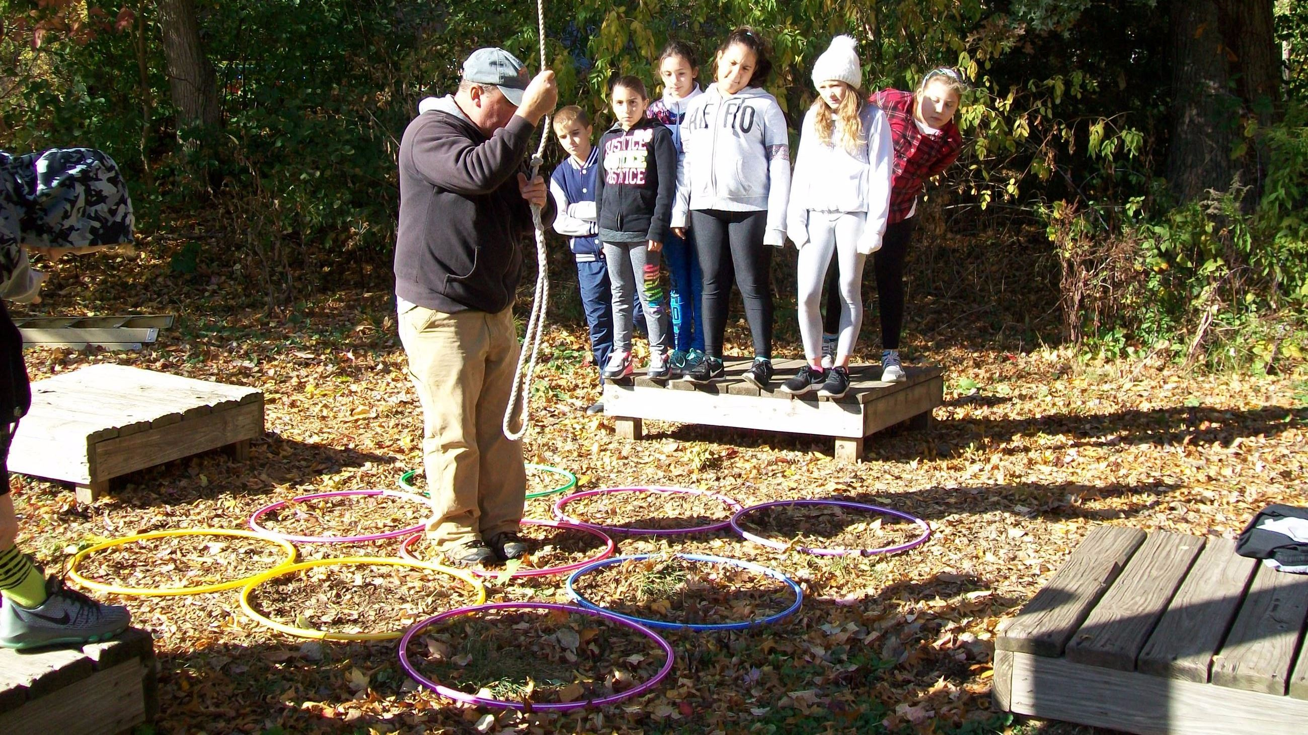 A group playing a game that uses a rope swing and low platforms