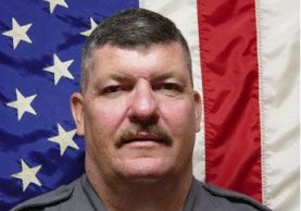 Portrait of Officer Peter Lavery with American Flag as backdrop