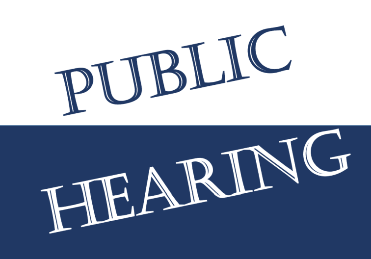 Blue and white sign with Public Hearing typed diagonally
