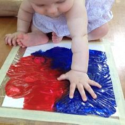 Baby fingerpainting red and blue paint