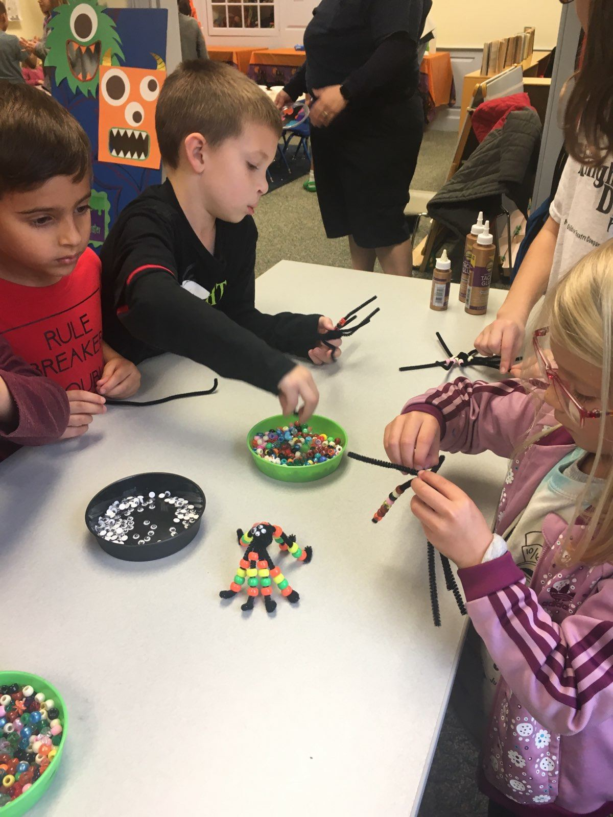 children making pipe cleaner spider crafts