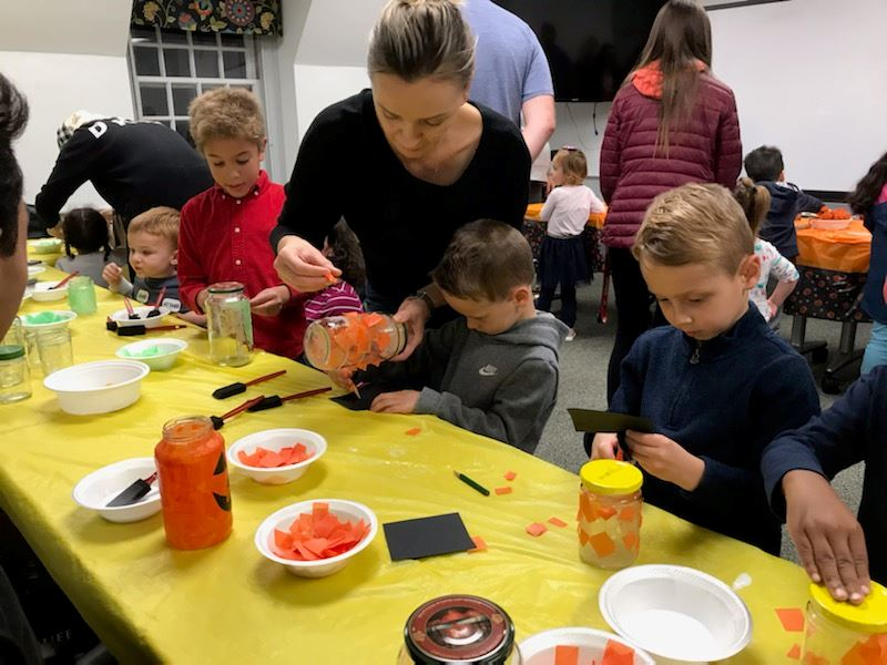 families making pumpkin luminaries with orange tissue paper and Mason jars