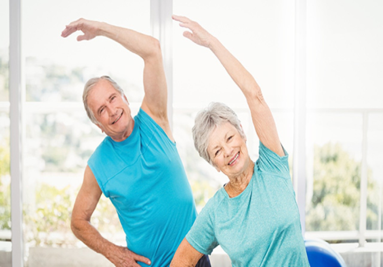 Photograph of two older adults streching thier arms over thier heads in exercise